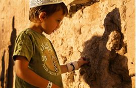 Picture of Picture of a child putting a note inside The Western Wall