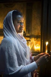 Picture of Picture of a woman holding a candle at Christian ceremony
