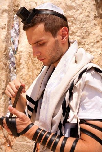 Picture of Picture of a young man putting on Tefillin