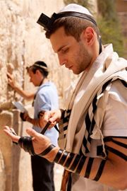 Picture of Picture of a young man putting on tefillin at the Western Wall