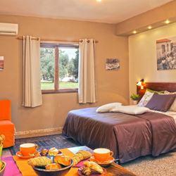 בית הארחה קיבוץ שמרת - חדר שינה עם מיטה זוגית ושולחן אוכל - Kibbutz Shomrat Guest House - Bedroom with double bed and dining table