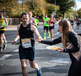 אצן מקבל חטיף מאישה בקהל, באמצע מירוץ - A Runner Receiving Food From A Woman On The Sidelines