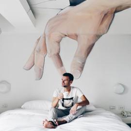"""ציור קיר של יד גדולה """"מחזיקה"""" באיש אמיתי היושב על מיטה תחתיה - A Wall Painting Of A Large Hand """"Holding"""" A Real Man Sitting On A Bed Under It"""