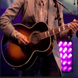 זמר עם גיטרה על הבמה - A Singer With A Guitar On Stage