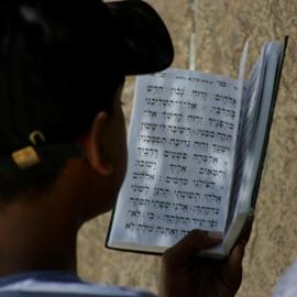 נער יהודי מתפלל מספר תפילה - A Jewish Boy Praying From A Prayer Book