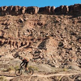 רוכב אופניים מול צוק במדבר - A Bicyclist In Front Of A Cliff In The Desert
