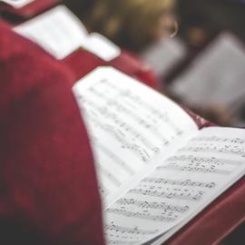 זמר במקהלה מחזיק ספר תווים - A Choir Singer Holding Music Sheets