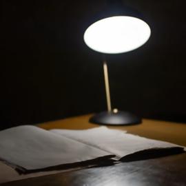 מנורת שולחן מאירה על מחברת - A Desk Lamp Shining On A Notebook